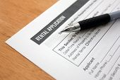 stock photo of rental agreement  - close up of rental application with pen - JPG