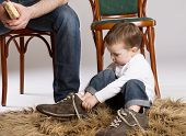 stock photo of big-foot  - Child is putting on a big father - JPG