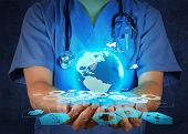 stock photo of cardiology  - Medical Doctor holding a world globe in her hands as medical network concept - JPG