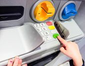 foto of automatic teller machine  - Minor at ATM machine pressing the green OK button - JPG