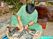 CU CHI, VIETNAM - NOVEMBER 17, 2013: Unidentified man makes shoes from old truck tires on November 1