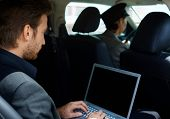 Young man in limousine working on laptop computer.