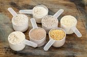 measuring scoops of gluten free flours - almond, coconut, teff, flaxseed meal, whole rice, brown ric
