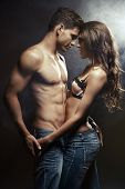 foto of studio  - Beautiful young smiling couple in love embracing indoor - JPG