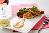 image of crab-cakes  - Two crab cakes appetizer garnished with spicy sauce green salad and raspbery - JPG