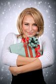 Closeup portrait of cute blonde woman hugging wrap gift box, isolated on gray snowy background, festive portrait, Christmas time concept