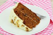 Carrot cake with walnuts and marzipan icing on pink napkin