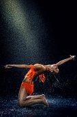 pic of dancing rain  - Woman dancing under rain in orange dress - JPG