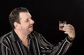 image of boose  - Unshaven man with a love watching glass brandy on black background - JPG