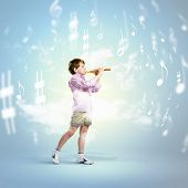 Image of little cute boy playing on flute against cloudy background