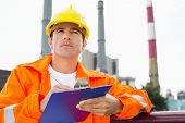 foto of headgear  - Male construction worker writing on clipboard at industry - JPG