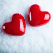 Two red glossy hearts on a frosty white snow background.  Love and St. Valentine concept.