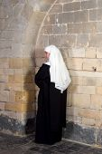 Young sister or nun waiting against the walls of a 14th century church