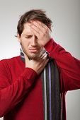stock photo of rhinitis  - Man in red sweater and scarf has a strong flu symptoms - JPG
