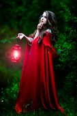 beautiful woman with red cloak and lantern in the woods