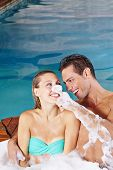 Happy young couple having fun in whirlpool with bubble foam bath