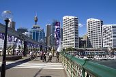 Pedestrians Crossing The Bridge At Darling Harbour.