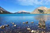 Mirror-smooth lake surrounded by mountains. On a large stone is a fancy dry driftwood, bleached by t