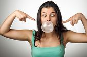 Pretty young girl with crossed eyes blowing a big chewing gum bubble