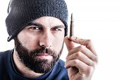 pic of extremist  - a bearded man wearing a beanie hat holding a sniper bullet and looking at it - JPG