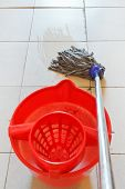 Mopping The Tile Floor By Swab And Red Bucket