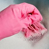 Hand In Pink Rubber Glove Wrings Out Wet Cloth