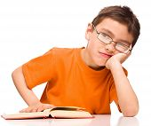 Little boy is tired to read his book, isolated over white