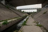 picture of sewage  - Sewage canal outdoors with dirty water flowing - JPG