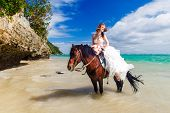 Happy Bride Walking With Horse On A Tropical Beach