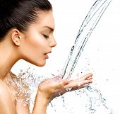Beautiful Woman with splashes of water in her hands. Beautiful Smiling model girl under splash of wa