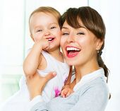Mother and Baby kissing and hugging at Home. Mum and her Child - Little Daughter. Happy Smiling Family Portrait