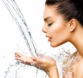 Beautiful Woman with splashes of water in her hands. Beautiful Smiling model girl under splash of water with fresh skin over blue background. Skin care Cleansing and moisturizing concept. Beauty face