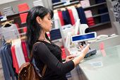 Girl pays to shop using mobile phone. NFC - Near field Communication. Mobile payment.