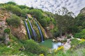 Three parallel streams of water running down the steep slope and fall in oval pool. Unusual three-jet waterfall in northern Israel