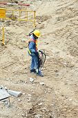 Building Worker At The Building Site Carrying An Electrical Cable