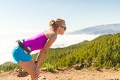 stock photo of canary  - Young woman cross country running in mountains on sunny summer day - JPG