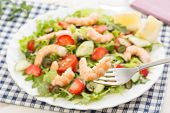 closeup of fork with fresh shrimp and berry salad with lettuce and rocket on background