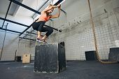 stock photo of training gym  - Fit young woman box jumping at a crossfit style gym. Female athlete is performing box jumps at gym.