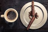 image of cigar  - the two defects in the morning. caffee and cigars. cigars mark the seven in the morning. the coffee is steaming hot. shot from above with objects placed on a wooden table