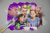Composite image of family celebrating a birthday with paintbrush dipped in purple paint against digitally generated grey background