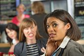 stock photo of outrageous  - Business woman worried about angry coworker in cafeteria - JPG