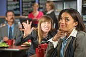 picture of outrageous  - Annoyed coworker behind smiling business woman in cafeteria - JPG