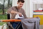 stock photo of hospice  - Horizontal view of a disabled man during ironing - JPG