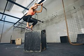 stock photo of jumping  - Fit young woman box jumping at a style gym - JPG