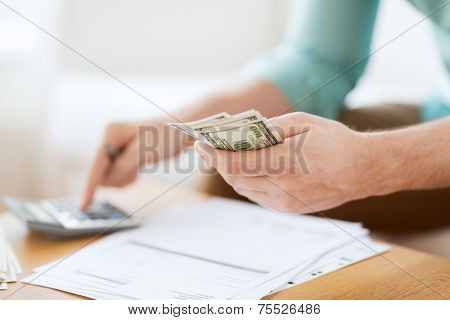 savings, finances, economy and home concept - close up of man with calculator counting money and mak