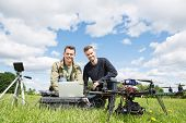 Portrait of men using laptop next to UAV octocopter and tripod against cloudy sky