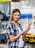 Portrait of female customer holding mobilephone and screwdriver in hardware store