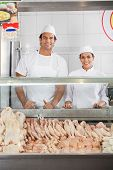 Portrait of confident male and female butchers smiling at display cabinet in shop