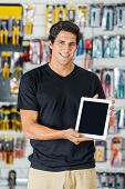 Portrait of smiling young man presenting digital tablet in hardware store