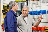 Senior male customer pointing while looking at vendor in hardware shop